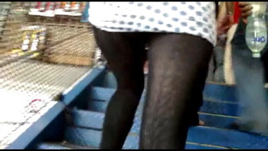 Girl with mini skirt and stockings climbing stairs